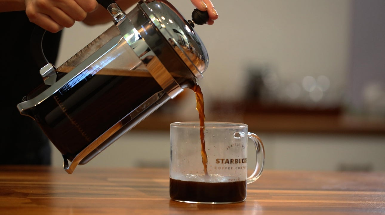 Pouring coffee out of a coffee press into glass coffee mug