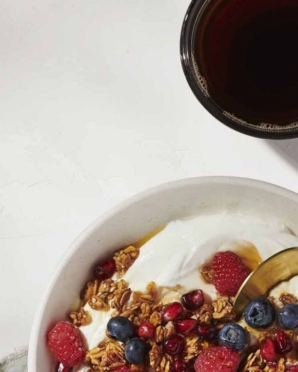 Cup of coffee and bowl of yogurt with fruit