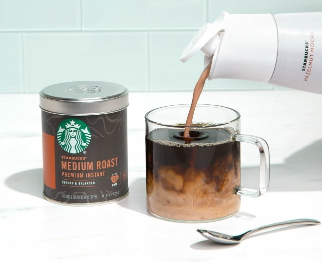 Pouring Starbucks creamer into cup of coffee